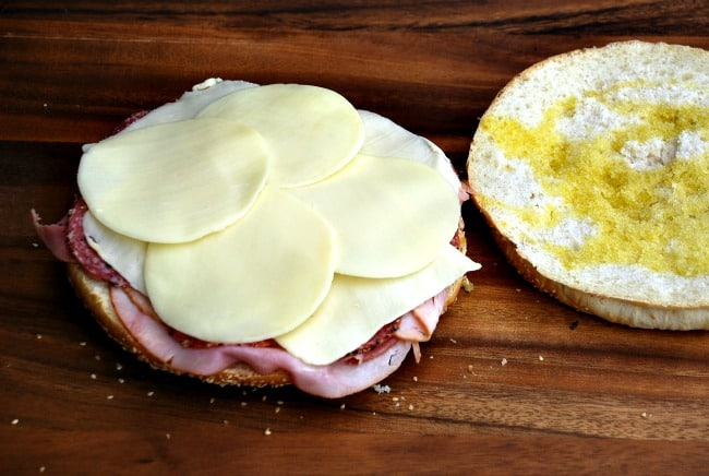 image: step by step muffuletta instruction photo. Adding cheese to the sandwich