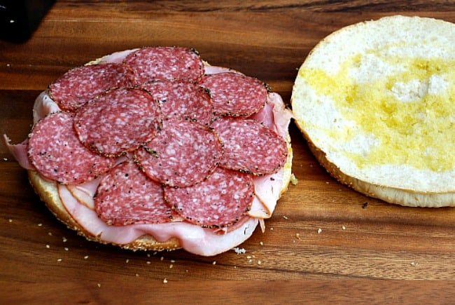 image: step by step muffuletta instruction photo. Adding capicola ham and salami to the bread