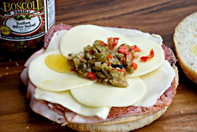 image: step by step muffuletta instruction photo. Adding olive salad to the sandwich