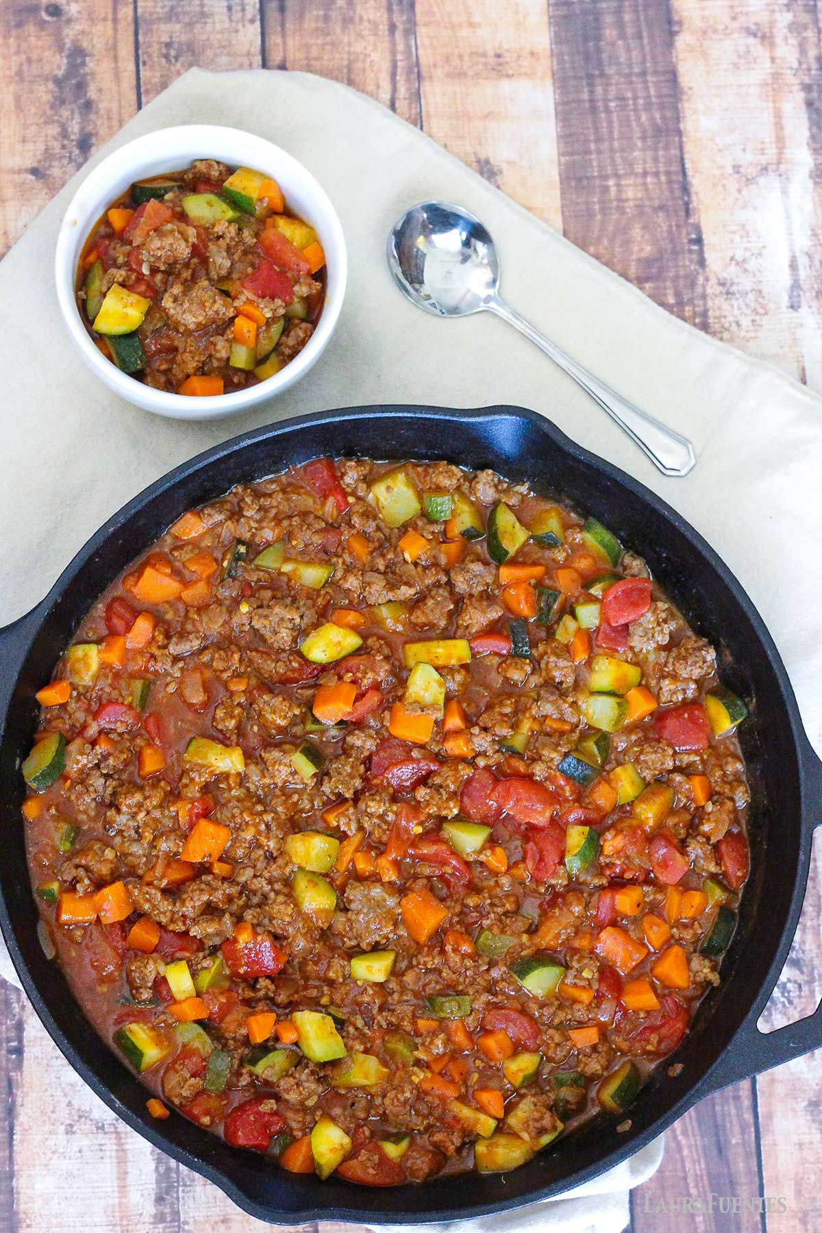 cast iron skillet full of meat and vegetable chili. Small white bowl of chili to the side of the skillet.