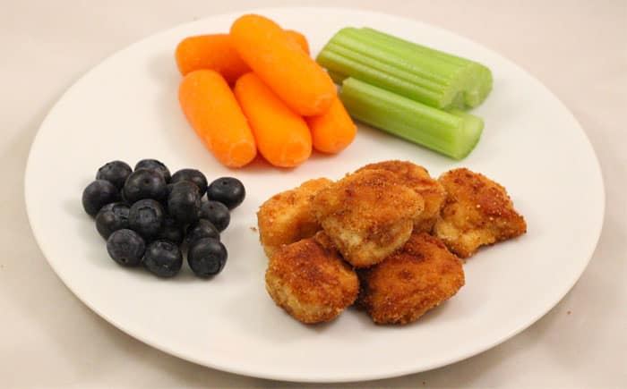 image: chicken nuggets on a plate with blueberries, carrot sticks and celery sticks
