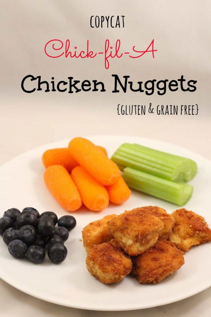 image: homemade chicken nuggets on a white plate with blueberries, carrot sticks and celery sticks. Image text reads - copycat chick-fil-a chicken nuggets {gluten & grain free}