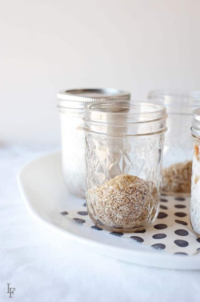 image: four mason jars, two filled with steel cut oats, two, lidded, with oats and milk.