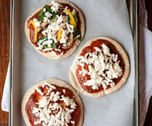pita pizzas about to go in the oven for a quick dinner the entire family will love