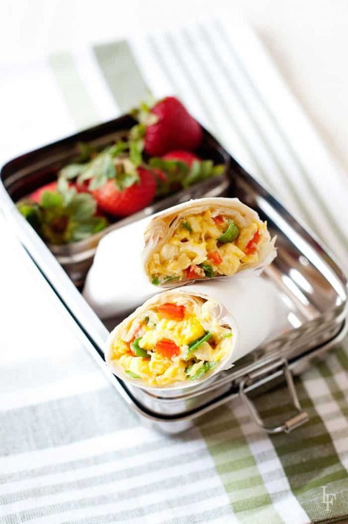 two breakfast burritos in a lunch tin with strawberries