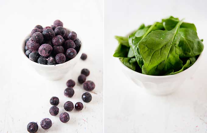 blueberries in a bowl and fresh spinach leaves in a bowl