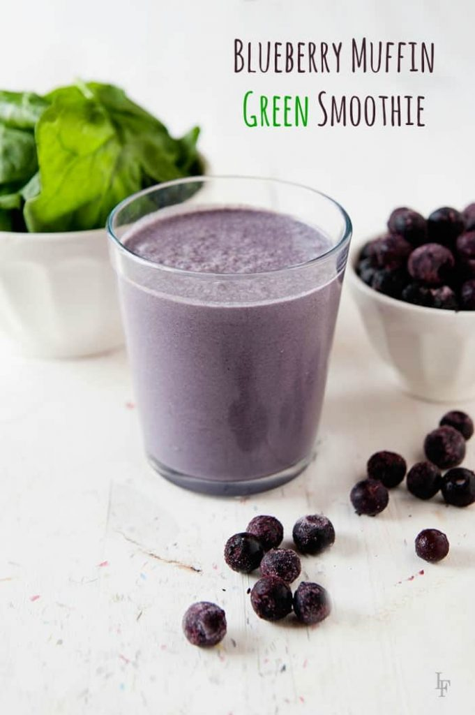 image:  purple smoothie in a glass with a small dish of spinach and frozen blueberries behind it.