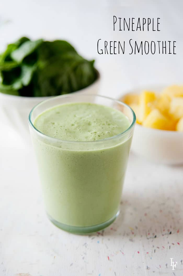 image: Glass cup filled with green smoothie. In the background a large white bowl of spinach leaves and a smaller bowl of cubed pineapple. Image text reads: Pineapple Green Smoothie