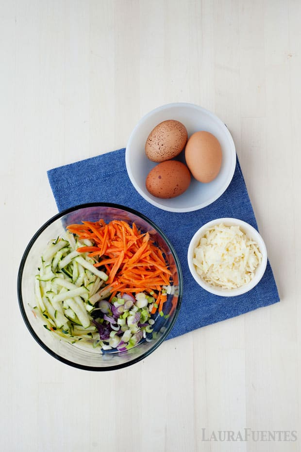 image: bowl of grated vegetables, next to bowl with three brown eggs and small dish of white shredded cheese
