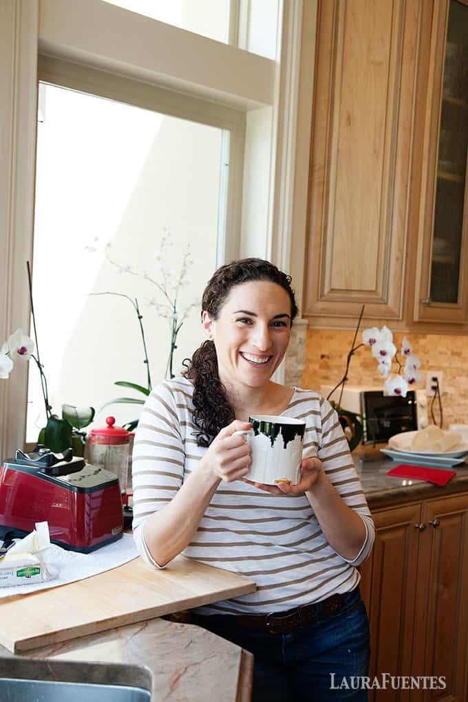 image: Laura in the kitchen holding a large cup of coffee