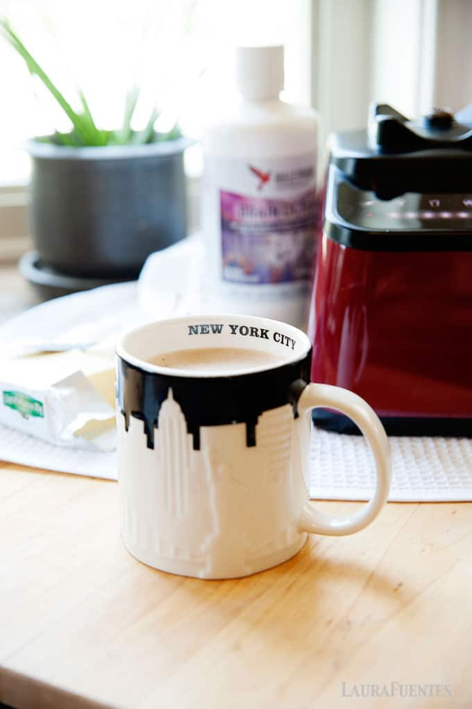 image: white and black NYC skyline coffee mug filled with coffee. Blender and bulletproof coffee bottle in the background.