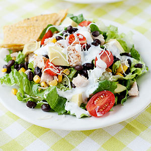 plate of salad with black beans, corn, chicken, and Ranch dressing