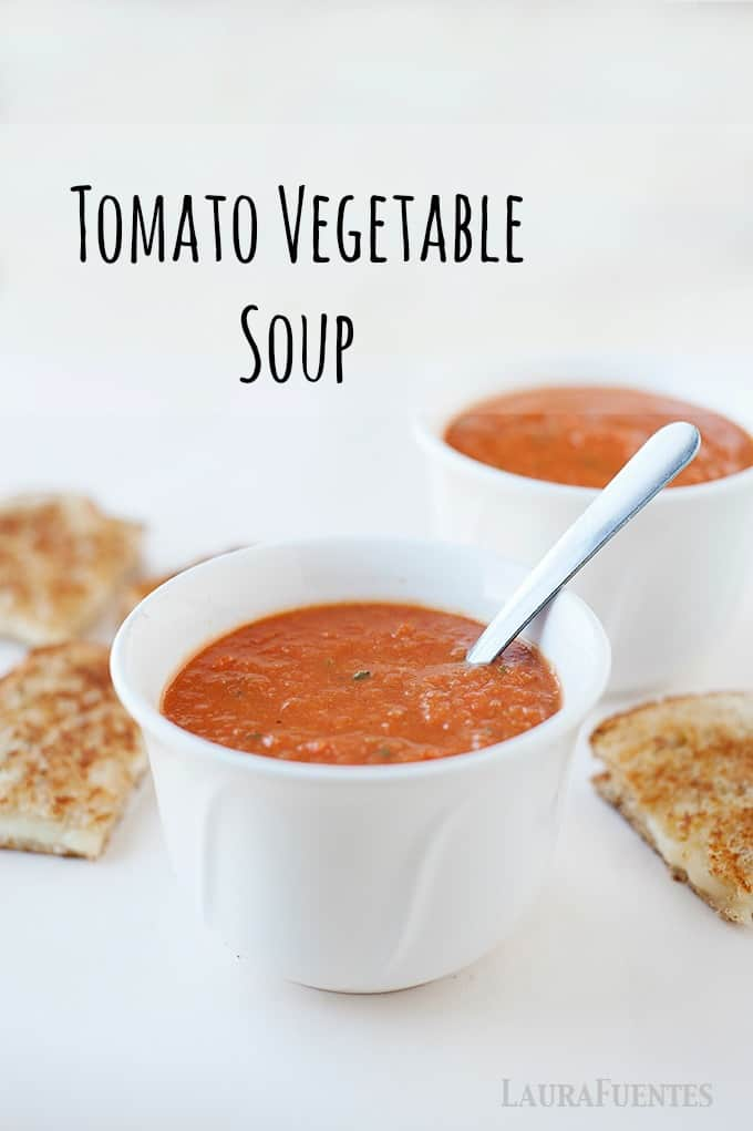 image: Two small bowls of tomato soup with grilled cheese. Image text reads: Tomato Vegetable Soup