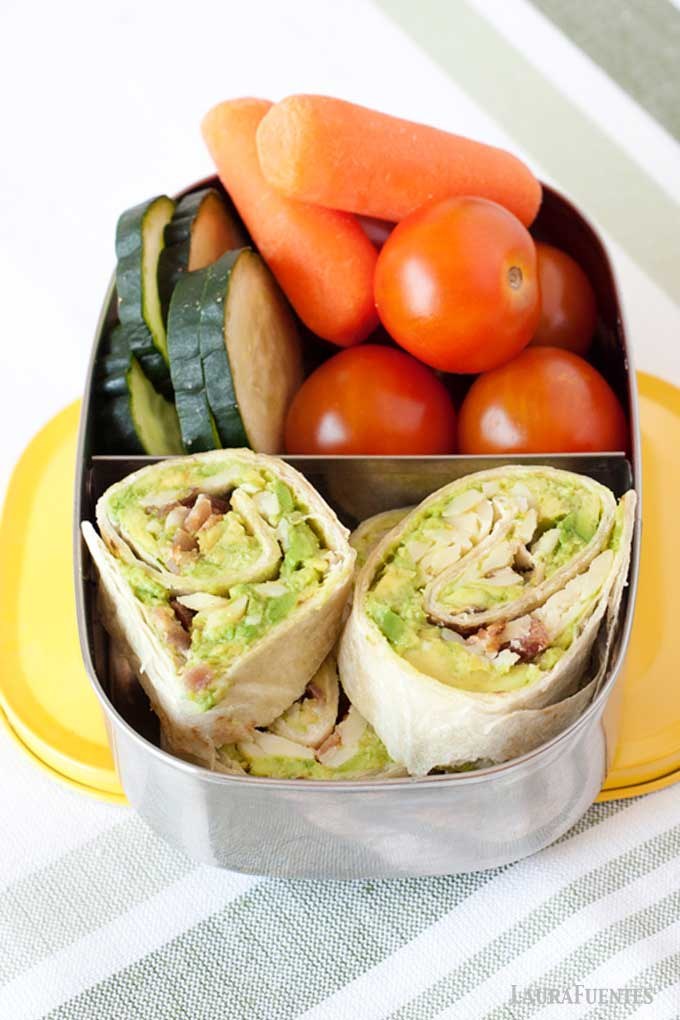 avocado pinwheels in a lunch container with fresh vegetables