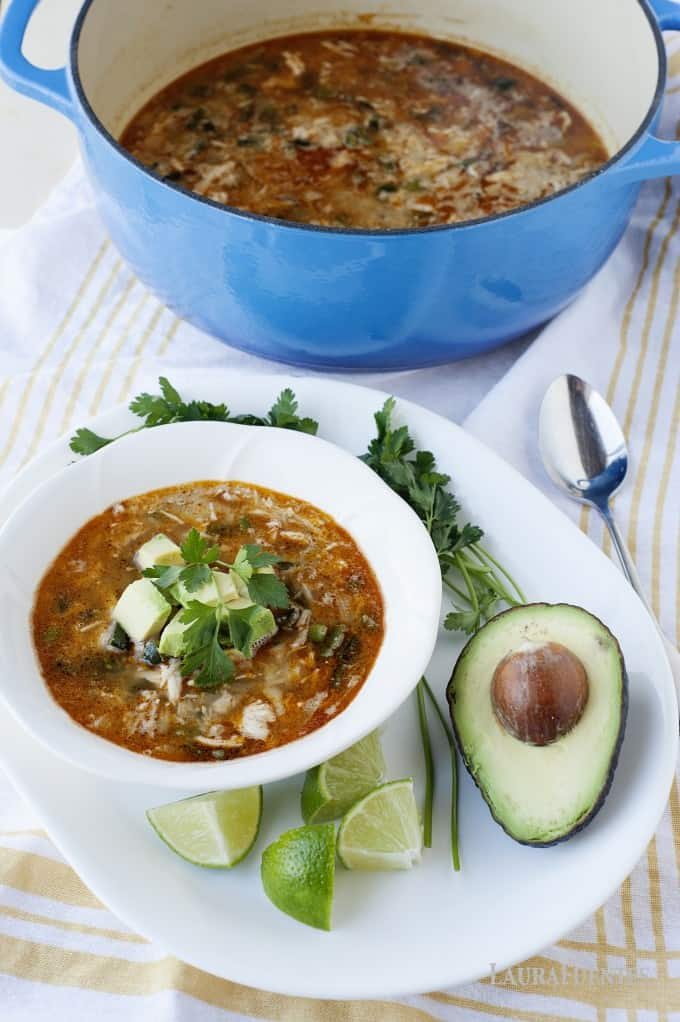 image: chicken chili in a bowl with a bright blue cast iron pot of chili in the backgroun