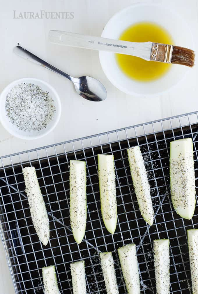 image: Zucchini sliced lengthwise with dish of melted butter and parmesan seasoning on the side.