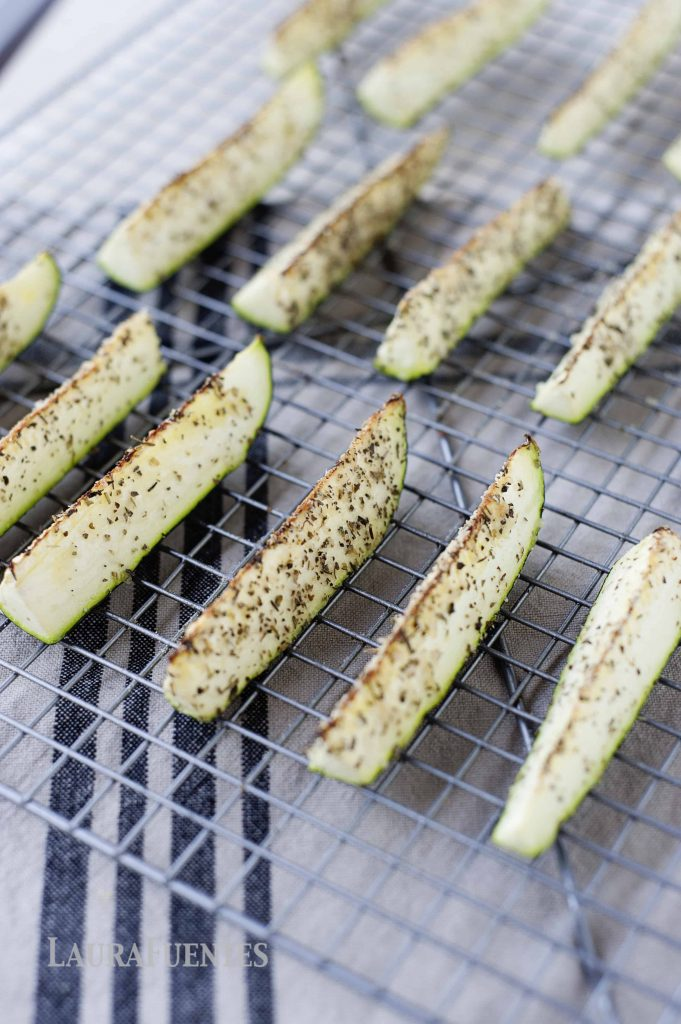 image: seasoned, baked zucchini sticks in rows on a cooling rack.