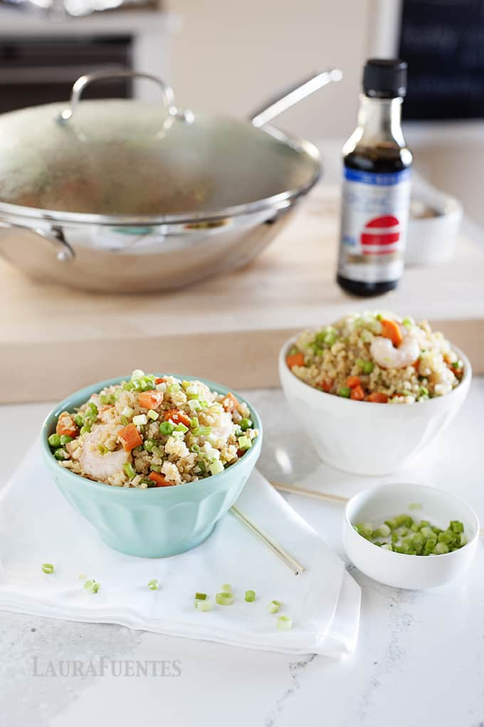 image: wok of cauliflower fried rice with shrimp. And two small bowls of the same.