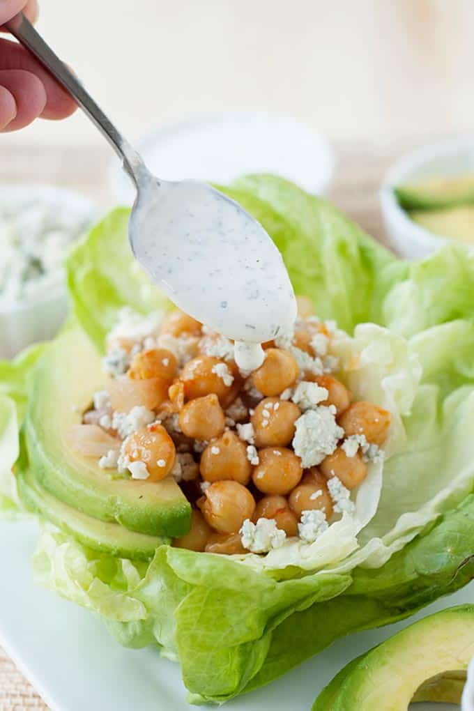 spooning ranch dressing over chickpeas and lettuce cups