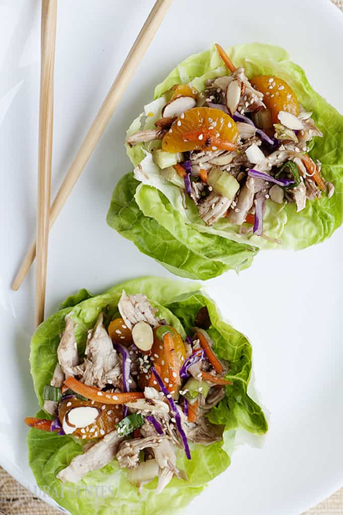 image: white plate with chopsticks, and two lettuce cups filled with asian chicken salad