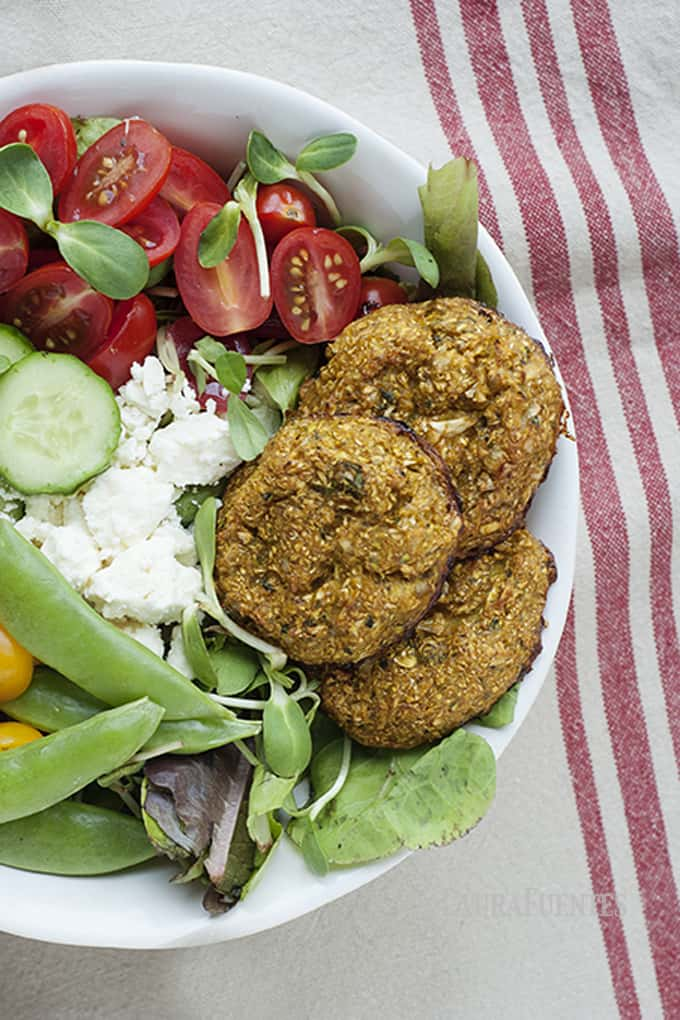 image: Bowl full of vegetables with three falafels