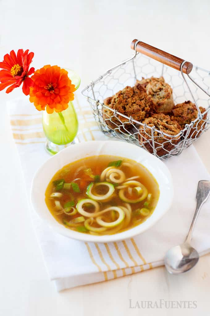 image: Ramen soup with zucchini noodles in a white bowl. A small basket of muffins behind the bowl.
