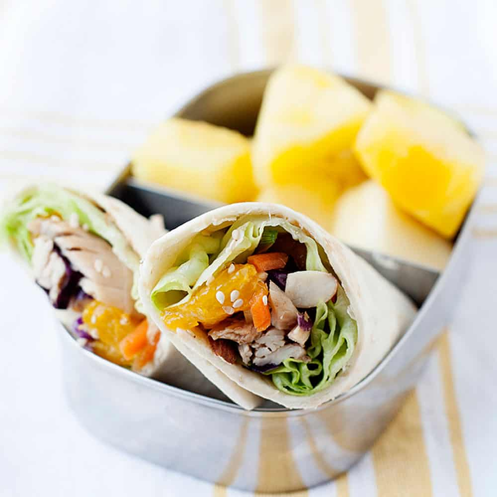 asian chicken salad wraps in small lunch container with fruit