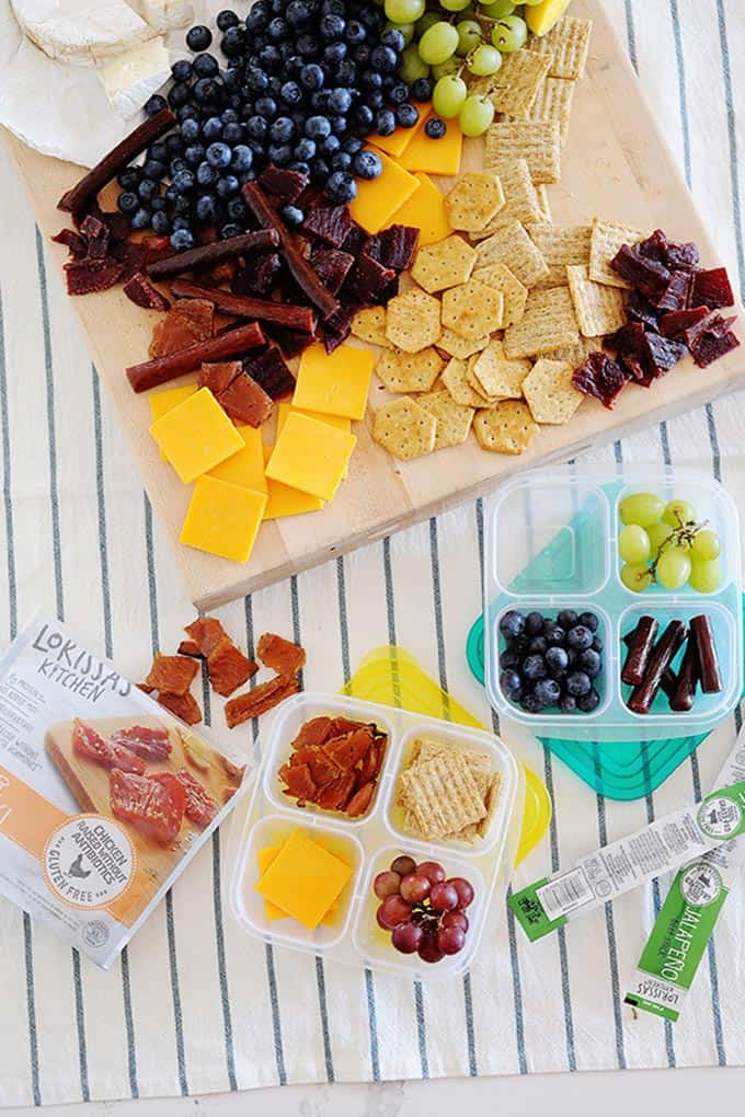 Snack board with fruit, cheese, and premium chicken cuts, jalapeno beef sticks, and crackers