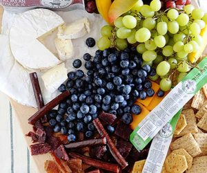 Charcuterie board with fruit, cheese, and premium chicken cuts, jalapeno beef sticks, and crackers