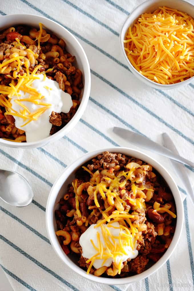 Image: Bowls of chili mac topped with cheese and sour cream.