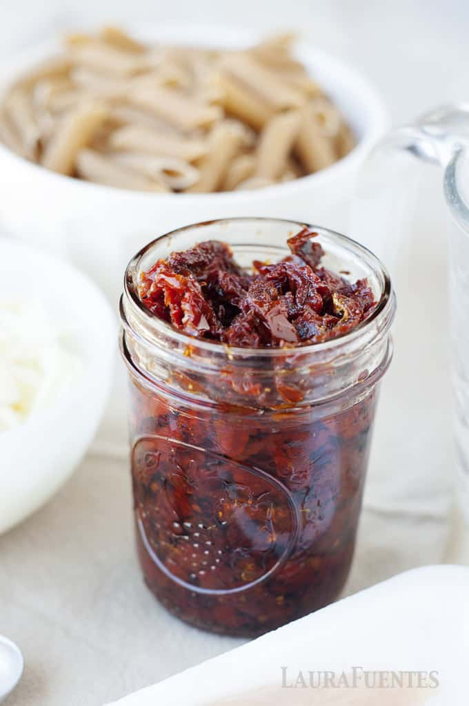 image: small glass jar filled with sun dried tomatoes.