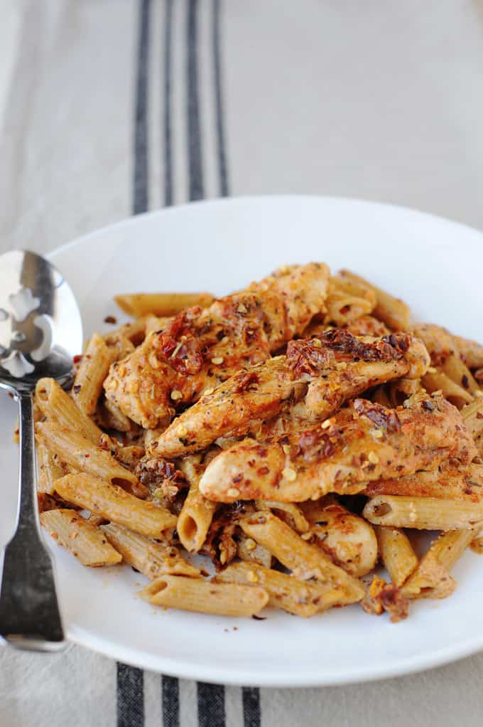 image: side view of white plate full of sun dried tomato pasta and chicken strips