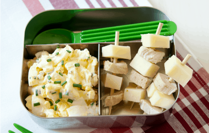 image: healthy lunch chicken and cheese skewers and egg salad in a tin lunchbox