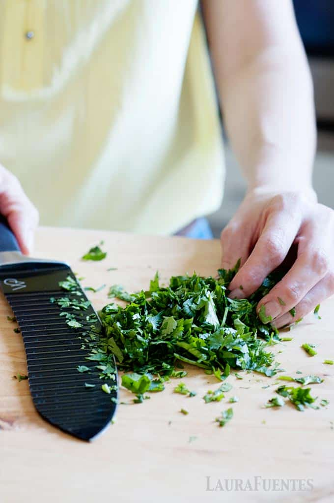 image: woman chopping cilantro into small pieces on a cutting board