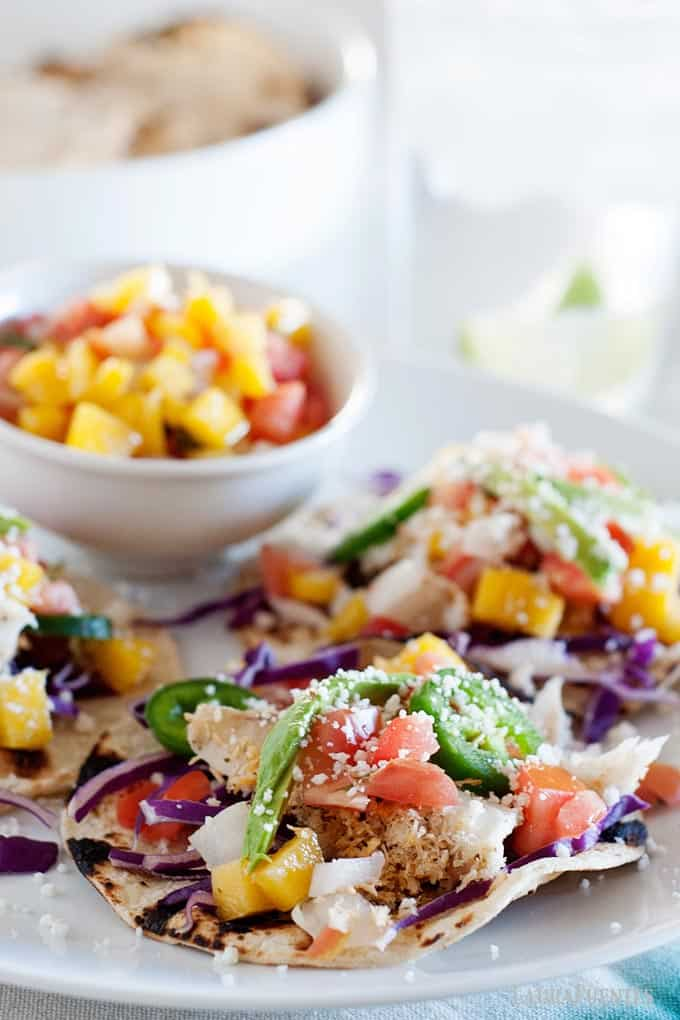 image: three fish tacos laying flat on a white plate. Small dish of pineapple pico de gallo in background.