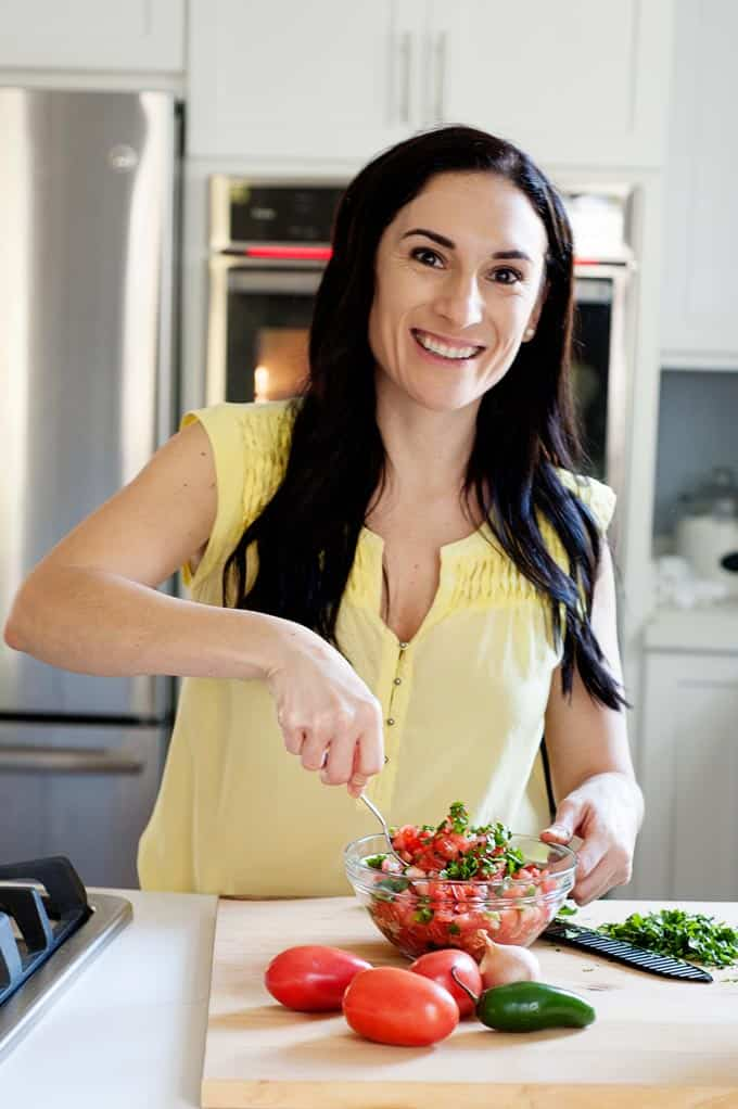 image: Woman scooping pico de gallo in a medium clear bowl. Whole Pico de Gallo ingredients on the cutting board next to her.