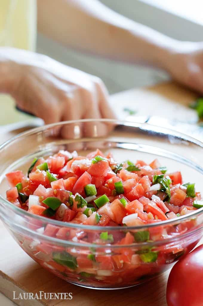 image: closeup of clear bowl filled with freshly made pico de gallo