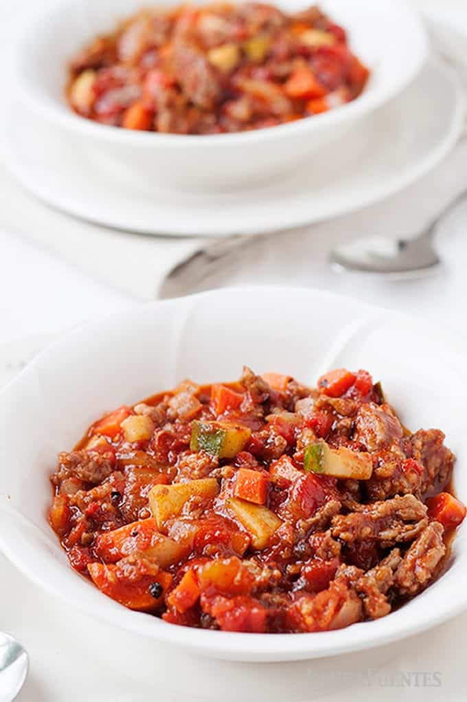 image: Two white bowls of no-bean meat and veggie chili on a white tablecloth