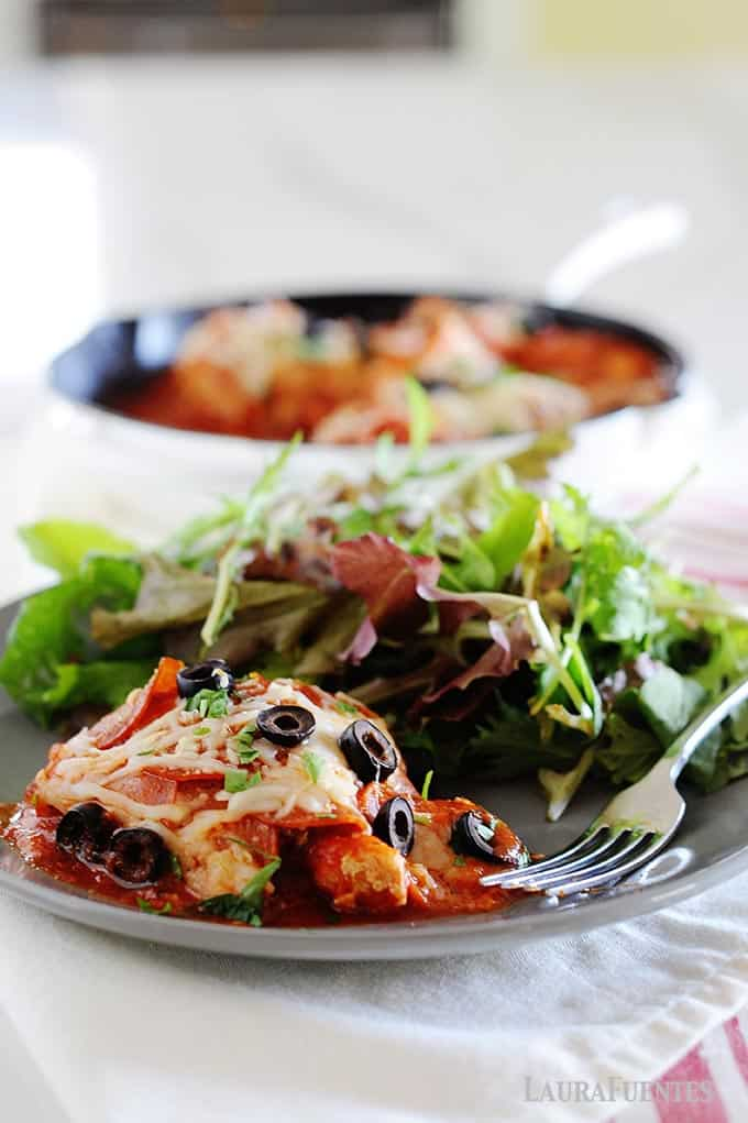 IMAGE: gray plate with pepperoni pizza chicken and large salad. Background of photo has skillet full of more pizza chicken.
