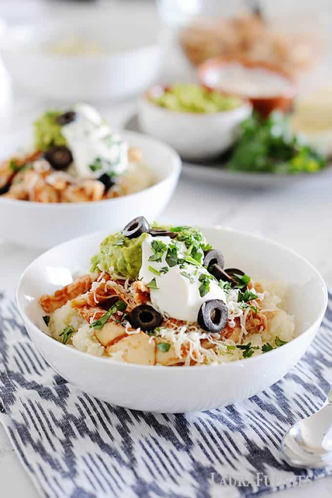 image: Two white bowls filled with cauilflower rice, chicken, shredded cheese, guacamole, sour cream and sliced olives