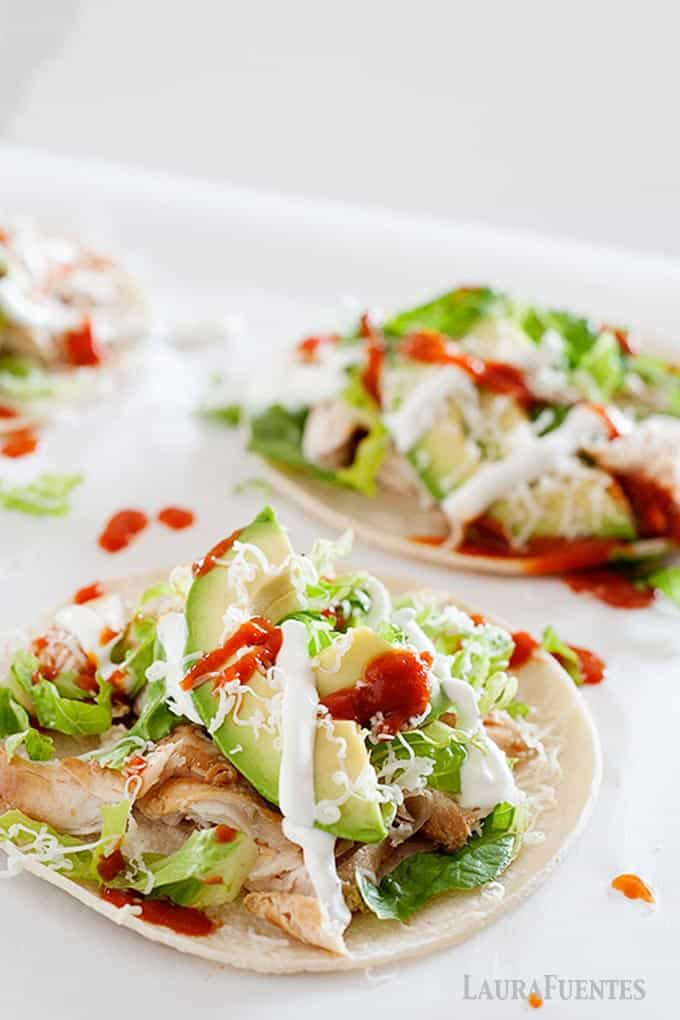 image: Flat chicken tacos topped with spicy red sauce, vegetables and cheese