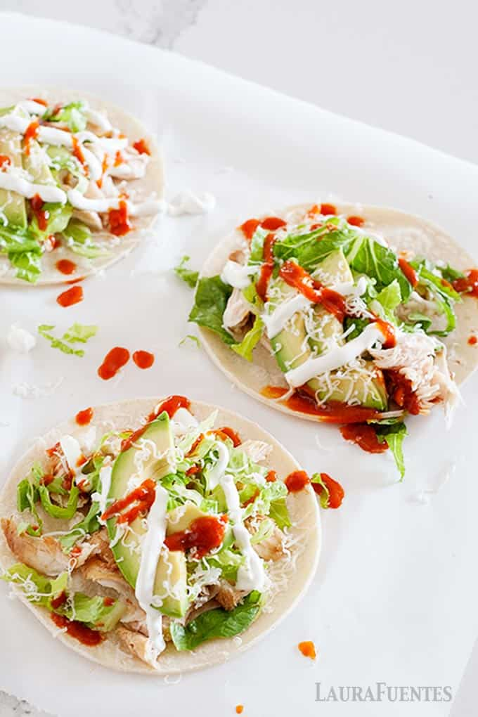 image: three flat chicken tacos with avocado slices, red and white sauces and shredded cheese