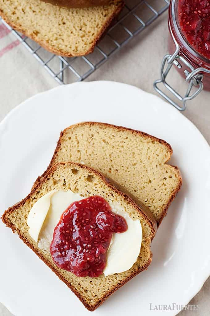 image: two slices of grain free bread on a plate, one topped with butter and raspberry jam.