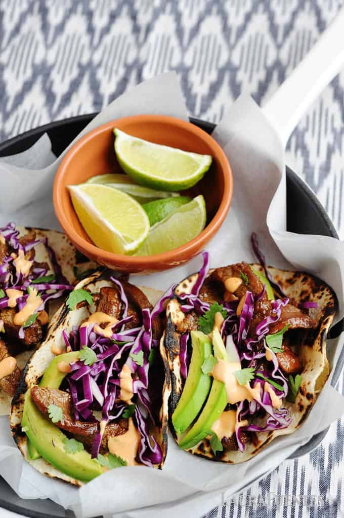 image: beef tacos with red cabbage and avocado slices, and a small orange bowl of lime wedges