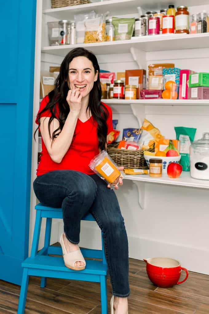 well stocked pantry with woman eating snacks in front