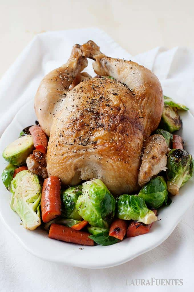 roasted whole chicken on plate with roasted vegetables