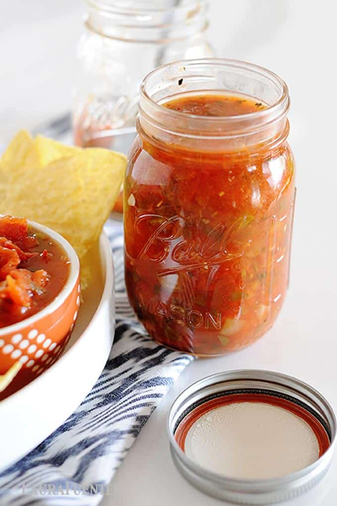 image: Open mason jar full of red salsa next to dish of corn chips and bowl of the same salsa