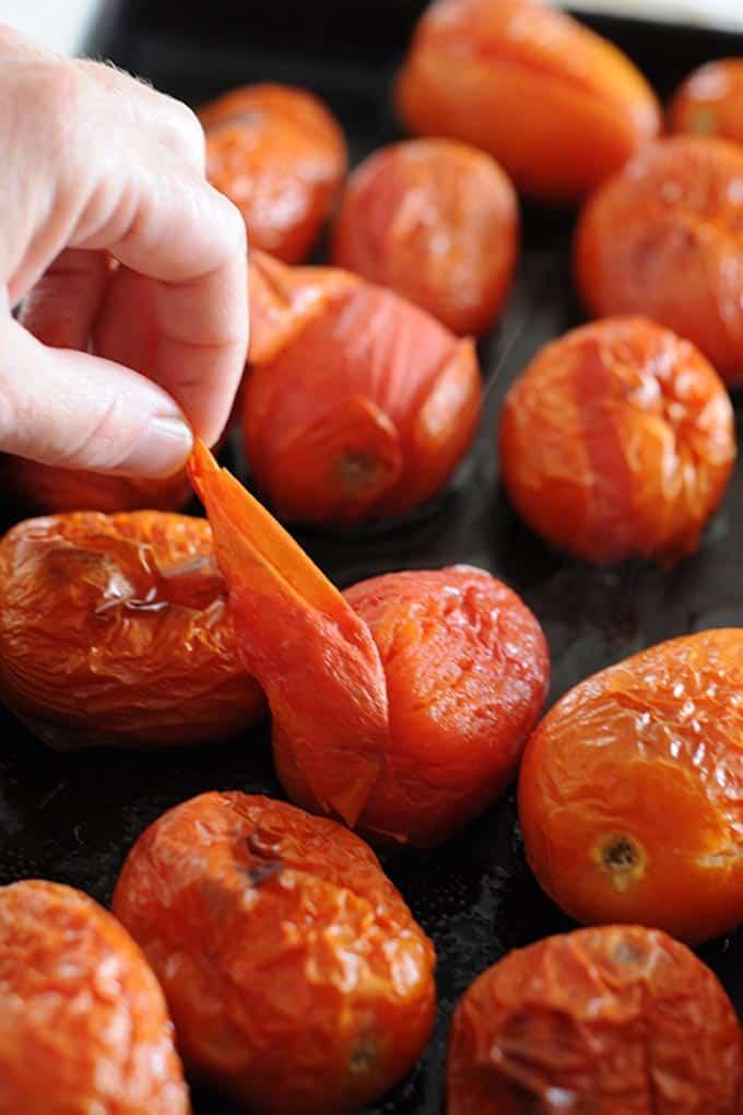 image: hand peeling skin off of roasted roma tomatoes