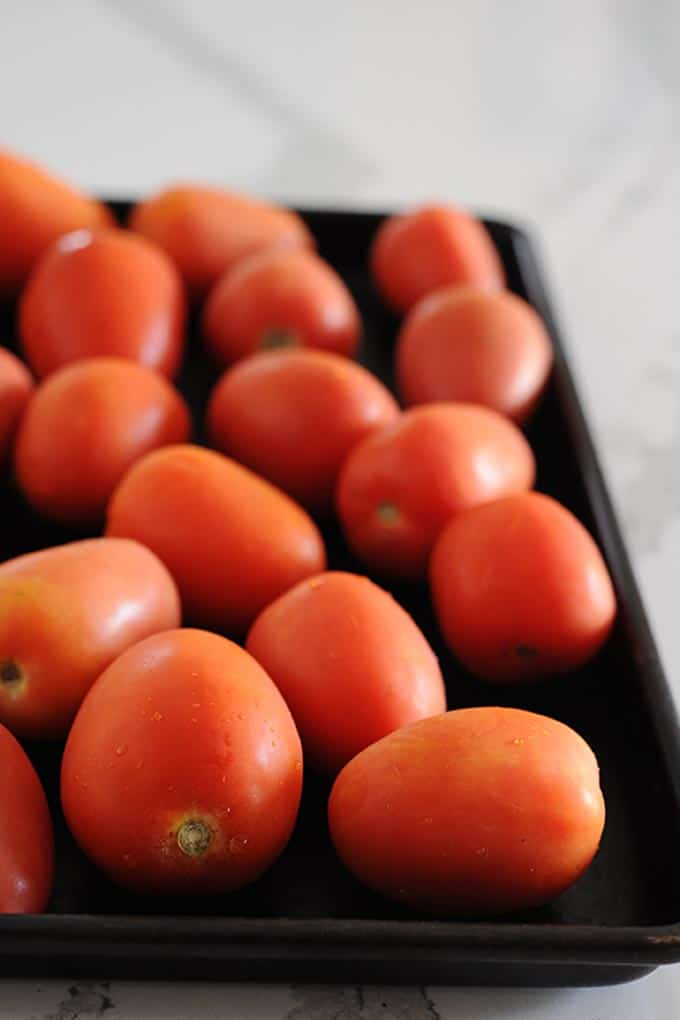 image: freshly washed roma tomatoes laid out on a roasting pan