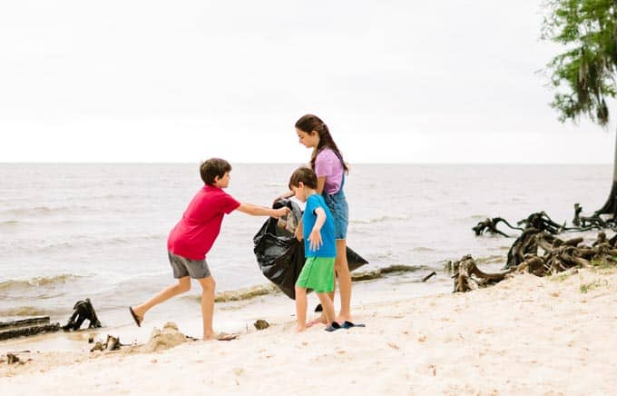 kids cleaning up trash on beach
